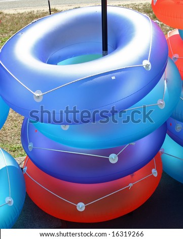 A stack of colorful inflatable rings in the sun - stock photo