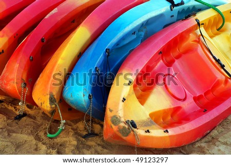 A stack of colorful sport kayaks in the sand of a beach - stock photo