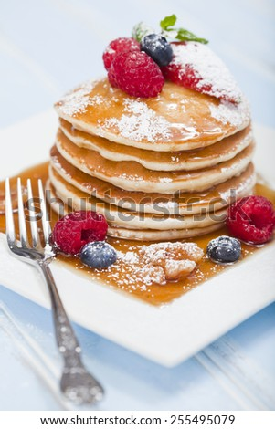 A stack of 6 cooked plain pancakes with fruit - stock photo