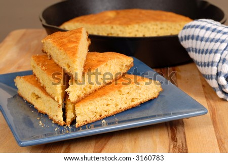 A stack of cornbread on a blue plate with skillet in background - stock photo