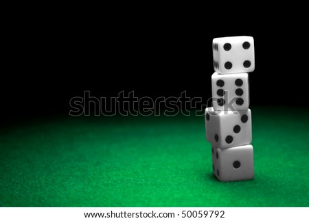 A stack of dice over a green felt table - stock photo