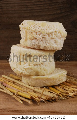 A stack of different frnch goats cheeses on a straw mat