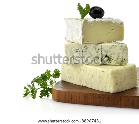 A Stack Of Different Kinds Of Cheese On A Cutting Board - stock photo