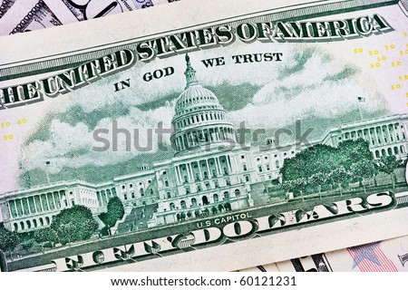 A stack of fifty 50 dollar bills fanned out with the back US Capitol showing on a white background - stock photo