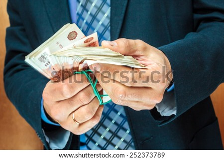 A stack of five thousandth bills in the men's hands.