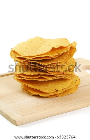 A stack of fried corn tortillas on a cutting board