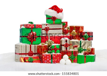 A stack of gift wrapped Christmas presents on snow, isolated against a white background. - stock photo