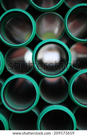 a stack of green pipes in a construction zone - stock photo
