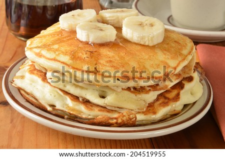A stack of home cooked pancakes with sliced bananas