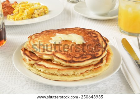 A stack of home made pancakes with scrambled eggs and bacon - stock photo