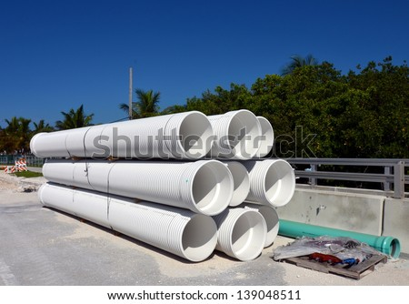 A Stack Of Large White Industrial PVC Sewer Pipes At A Road Construction Site - stock photo