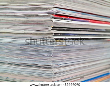 A stack of magazines filling the frame from top to bottom focus on corner edge - stock photo
