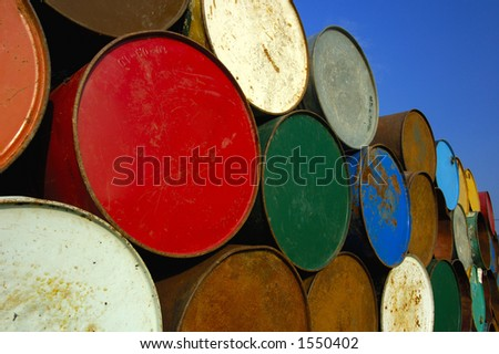 A stack of multi-coloured oil barrels, towering in to the clear blue sky. Space for text in the sky. - stock photo