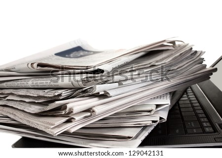 A stack of newspapers lying on black laptop keyboard - stock photo
