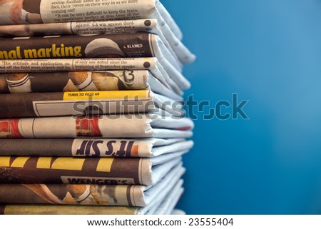 A stack of newspapers with a blue background - stock photo