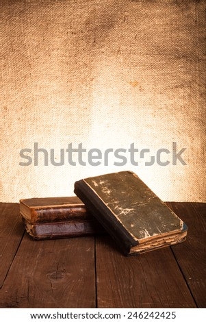 A stack of old books on old wooden table against the background of burlap. - stock photo