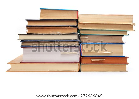 A stack of old books with bookmarks in different directions on different pages. - stock photo