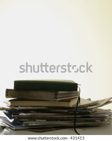 A stack of old magazines and diaries on a white table with a white background and extra space