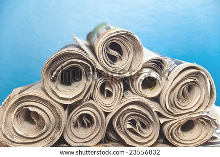 A stack of old rolledup newspapers with a blue background - stock photo