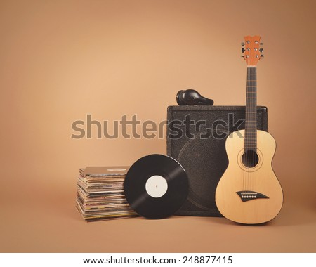 A stack of old vinyl records and acoustic wooden guitar with an amplifier are isolated on a brown background for a music or band concept. - stock photo