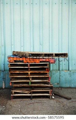 A stack of old wooden pallets painted in bright colors, next to the blue corrugated metal wall of an old factory building. - stock photo