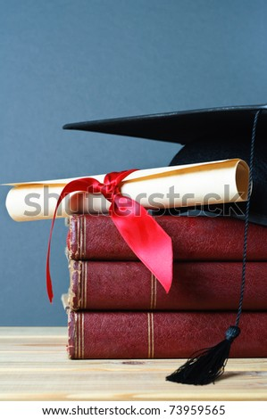 A stack of old, worn books with a mortarboard and ribbon tied scroll on top, placed on a wooden table with a grey background. - stock photo