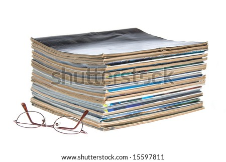 A stack of old worn magazines with reading glasses isolated against a white background.