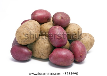 A stack of ordinary and red skinned potatoes.  On a white background. - stock photo