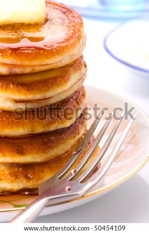A stack of pancakes on a plate with syrup fruity and butter - stock photo
