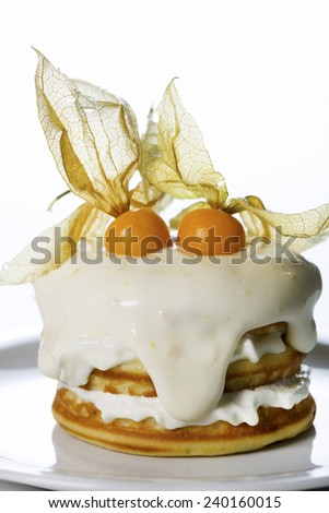 a stack of pancakes with cream and decorated with physalis on white background - stock photo
