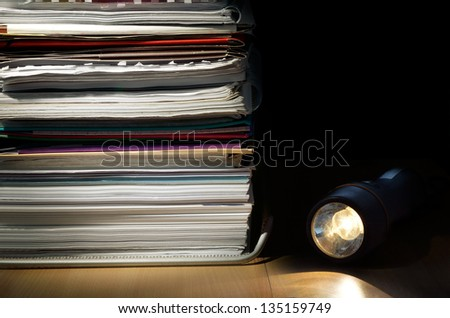 A stack of papers and a flashlight on a desk in a low light scene - stock photo