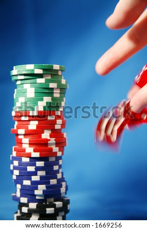 A stack of poker playing chips and a rolling die - stock photo