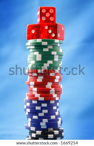 A stack of poker playing chips with dice - stock photo