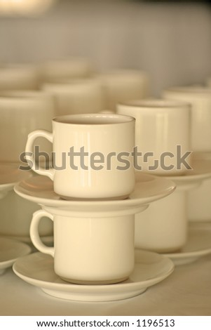 a stack of porcelain cups, shallow depth of field, warm colour filtering. - stock photo