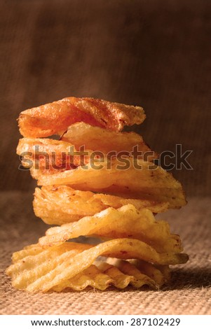 A stack of potato chips with warm side light. Vertical format on a burlap surface. - stock photo
