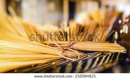 A stack of raw dry uncooked delicious italian spaghetti pasta bow in braided basket - stock photo