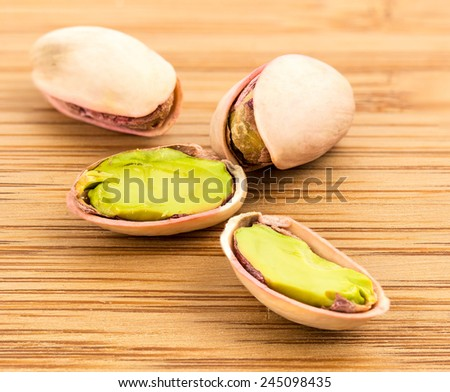 A stack of roasted pistachios on wood . - stock photo