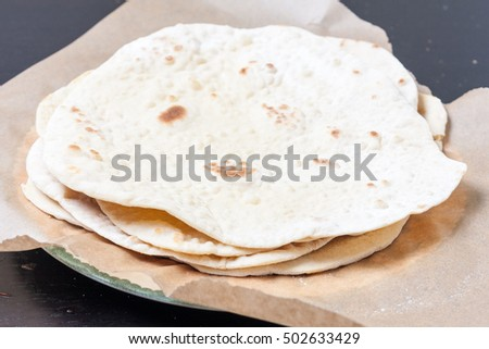 A stack of rotis on a sheet of baking parchment