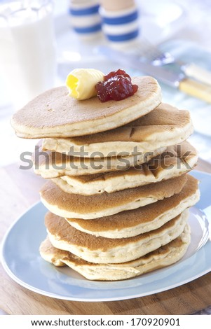 A stack of Scotch Pancakes topped with jam and butter on a breakfast table