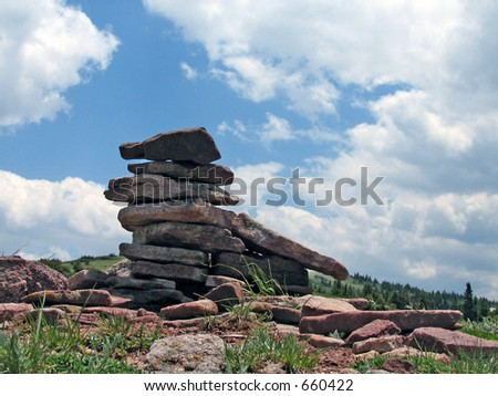 A stack of small boulders at the top of a mountain near the clouds.