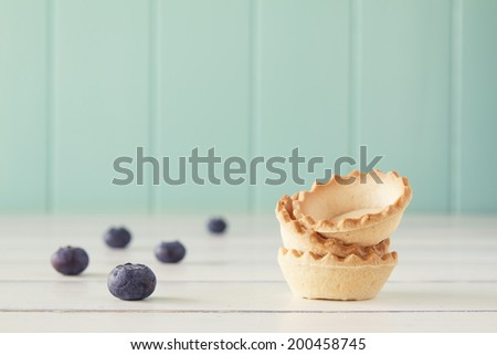 A stack of tartlets and several blueberries on a white wooden table with a robin egg blue background. Vintage Style. - stock photo