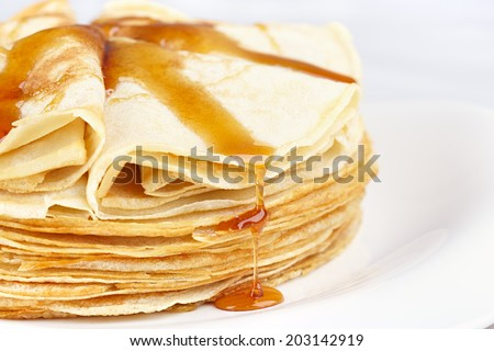 A stack of thin pancakes with honey - stock photo