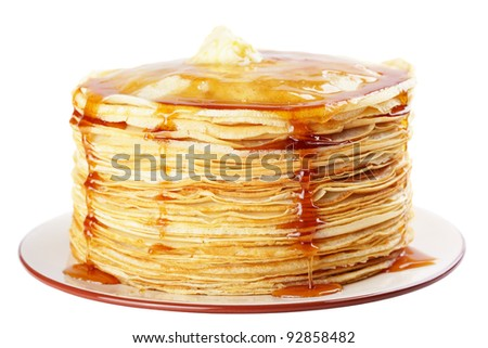 A stack of thin pancakes with honey and butter - stock photo