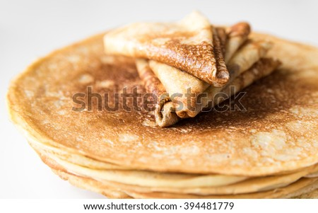 A stack of thin Russian pancakes and crepes folded triangle, close-up, isolated - stock photo