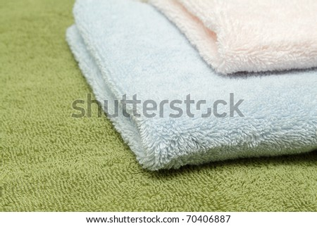 A stack of three bath towels of different colors - stock photo
