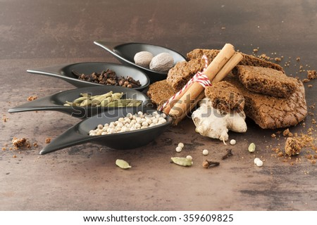A stack of traditional dutch speculaasbrokken. And spoons filled with spices: cloves, ginger, cardamom, cinnamon, white pepper, nutmeg