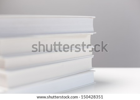 A stack of white books photographed over a white surface with gray background. Shallow DOF. - stock photo