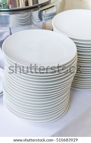 A stack of white dishes ready for use, stack of white plate ready to served