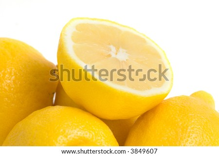 A stack of whole and cut lemons on white.