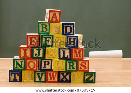 A stack to color wooden blocks of the alphabet in front of chalkboard, Schools Days